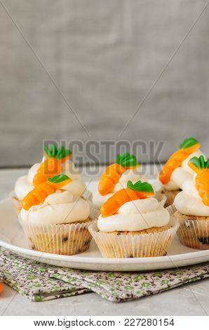 Vanilla Cupcakes With Chocolate Chips And Cream Cheese Frosting Decorated With Carrot Marmalade.