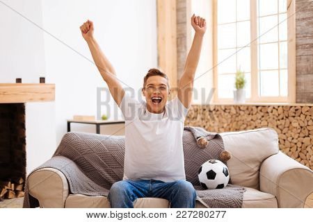 Football Fan. Good-looking Delighted Well-built Adolescent Smiling And Holding His Arms Up While Sit