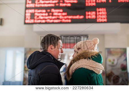 Couple Of Travelers In Warm Clothes In The Waiting Room At The Hall Of Station Near The Scoreboard W