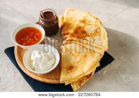 Delicious Crepes (blinis) With Assorted Sauces On A Wooden Plate On A White Stone Background.