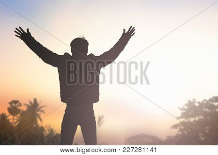 Soft Focus And Silhouettes Of Man Raise Hand Up Worship God Against Blurred Sunset Sky