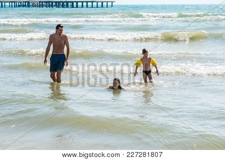 Mum, Son And Dad Splashong And Swimming In Sea Waves. Boy In Water Wings