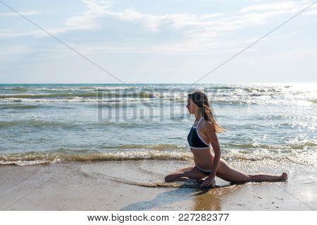 Woman Bruenette With Long Hairs In Blue Bikini Is Stretching On The Seashore. Side View. Eka Pada Ra