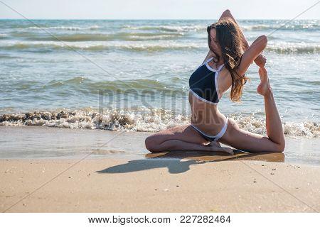 Woman In Bikini Practice Yoga Eka Pada Rajakapotasana Royal Pigeon Pose At Seaside, Close-up View.