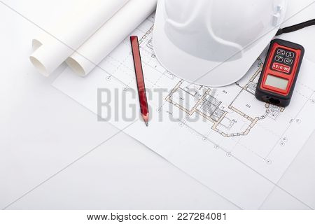 Architectural blueprints, safety helmet, laser distance meter,  pencil on a white background. Architect workplace. Engineering tools. Top view.