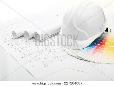 Architectural blueprints, safety helmet, color guide on a white background. Architect workplace. Engineering tools