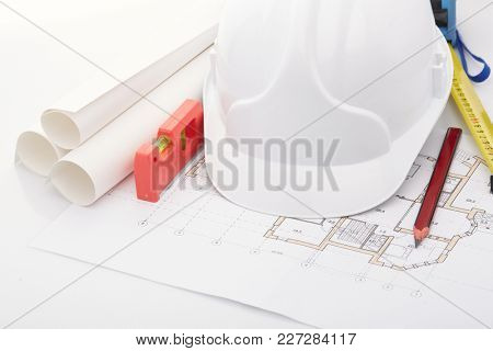 Architectural blueprints, safety helmet, building level, ruler and pencil on a white background. Architect workplace. Engineering tools. Top view.