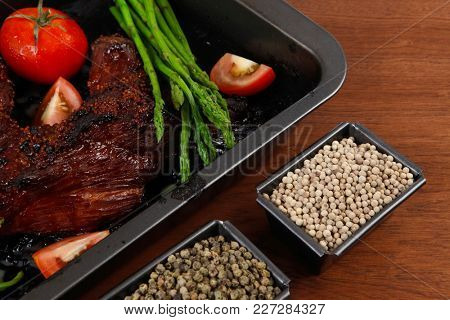 fresh glazed baked big beef meat rib chunk under sweet sauce with tomatoes hot chili pepper asparagus different peppercorn spices in black deep tray on light walnut wooden table