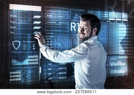 Positive Man. Cheerful Emotional Bearded Man Standing In His Convenient Equipped Office And Smiling