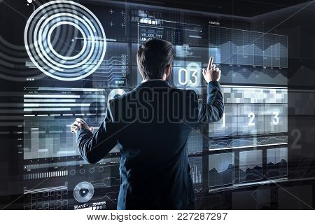 Important Numbers. Calm Qualified Experienced Programmer Pointing To His Futuristic Transparent Devi
