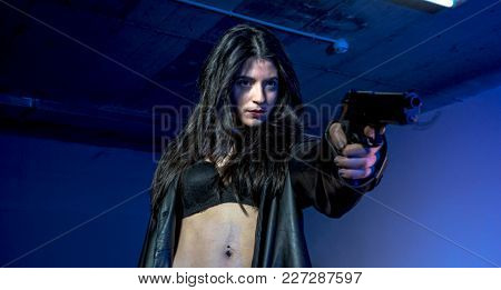 armed and dangerous girl in a parking lot, wearing a black leather jacket and a bulletproof vest