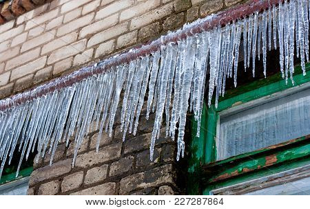 big icicles on an old building wall