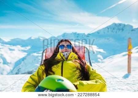 Photo of sports woman with helmet resting on armchair in winter resort
