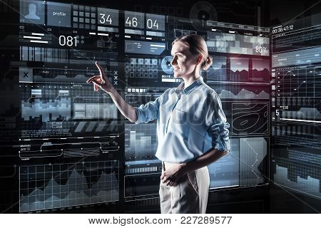 Clever woman. Calm clever cheerful programmer smiling and pointing to the information on a transparent screen while working with a futuristic device poster