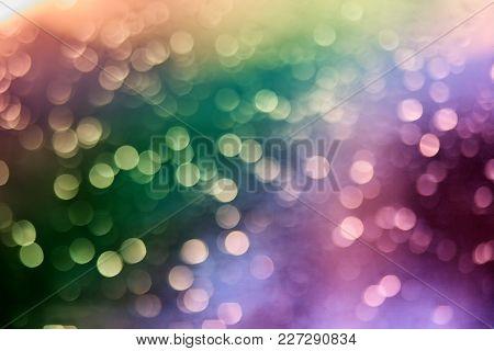 Defocused Of Multicolor Led Light On Black Background. Bokeh Photo Of Led Light. Green And Purple. O