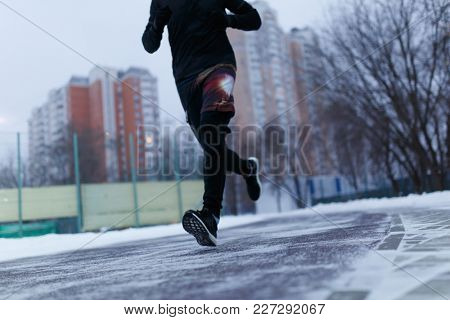 Picture of athlete running at stadium in winter