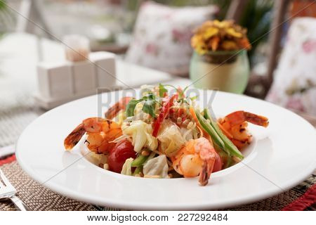Starter with fried shrimps and raw vegetables, light summer dish, restaurant table outdoors