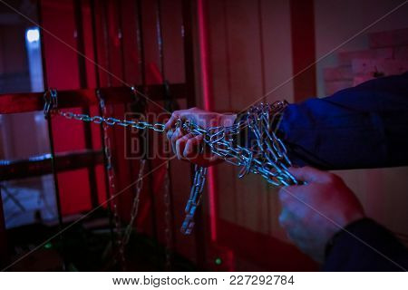 Hands Of A Man Pull A Heavy Container By A Chain In A Dark Room With Red Light