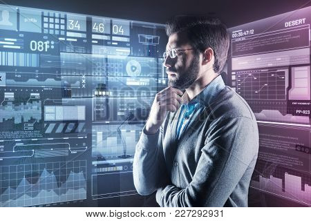 Serious Decision. Calm Attentive Clever Programmer Thoughtfully Touching His Beard While Standing In