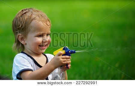 Little Boy Playing With Water Spray On Hot Summer Day. Funny Summer Games For Kids.
