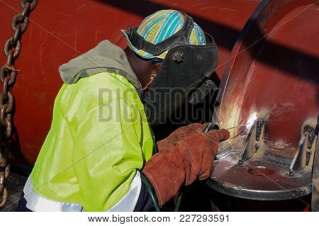 Man Welding Metal On A Construction Site, Tradesman Working With Welding Torch