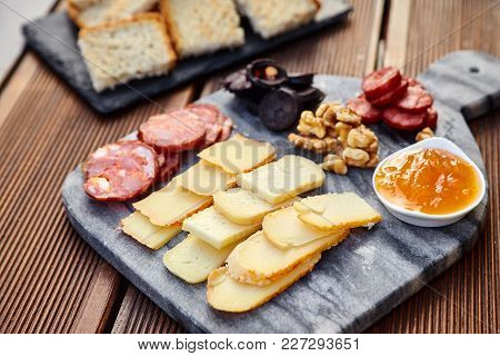 A Set Of Various Cheeses, Smoked Sausage, Apricot Orange Sauce, Walnuts, Blood Sausage And Fried Bre
