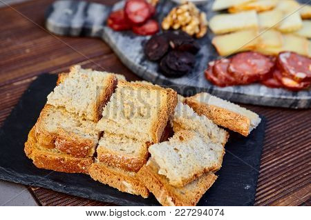 Fried Crusty Bread On A Background Of A Set Of Various Cheeses, Smoked Sausage, Apricot Orange Sauce