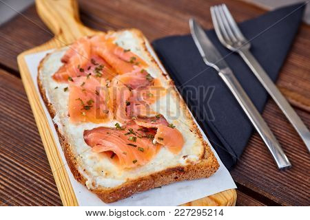 A Sandwich With Melted Cheese And Slices Of Salmon On A Light Cutting Board And A Brown Wooden Table