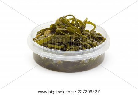 Salad Of Marinated Sliced Laminaria With Vegetable Oil And Spices In Round Plastic Container On A Wh