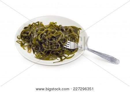 Salad Of Marinated Sliced Laminaria With Vegetable Oil And Spices On The White Dish With Fork On A W