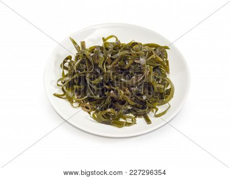Salad Of Marinated Sliced Laminaria With Vegetable Oil And Spices On The White Dish On A White Backg