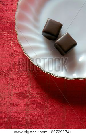 Two chocolates in a white glass plate over a red towel covering a table