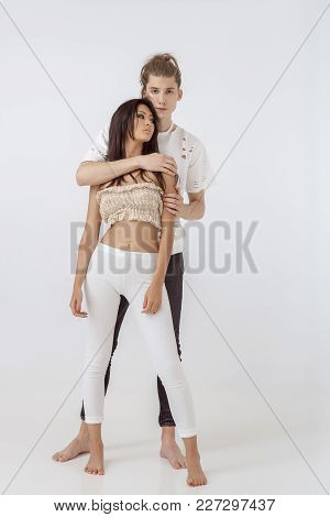 Fashionable Young Mixed-race Couple Indoors Standing In Studio Against White Background. Interracial