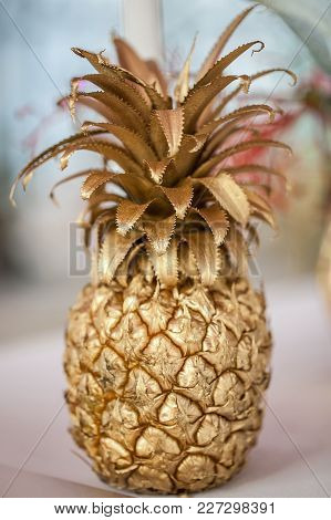 Table Decorations With Pineapple At Night Time Event With Candles In Background. Golden Pineapple Ta