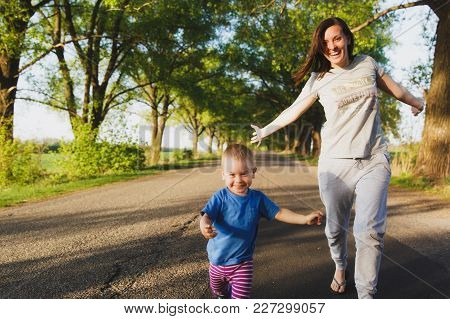 Young Woman, Little Cute Child Boy Walk On Road With Trees On The Roadside, Catch Up, Run In Warm Su