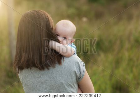 Young Tender Brunette Woman Standing At Green Grass Background Hugging Little Cute Child Baby Boy On