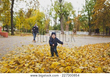Young Woman Walk In Fall Park With Little Cute Child Baby Boy, Catch Up, Run In Dry Yellow Autumn Le