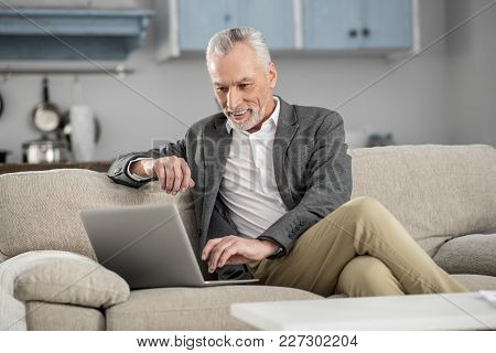 Express Positivity. Cheerful Man Keeping Smile On His Face And Leaning On Sofa While Looking At His