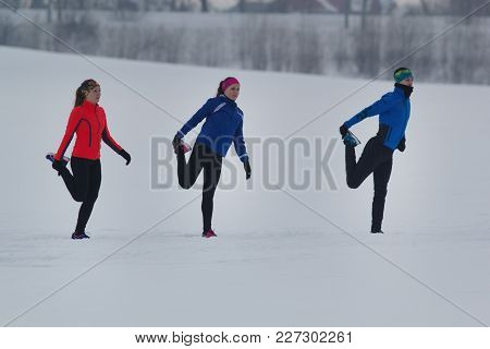Group Of Athletes Warming Up And Stretching Before Exercise In Winter Forest, Sport And Leisure Conc