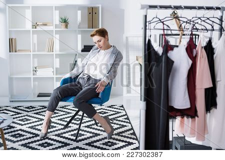 Stylish Fashion Designer Sitting In Chair At Modern Office