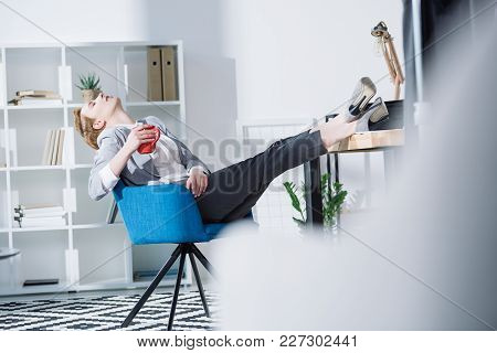 Fashionable Young Businesswoman Relaxing With Cup Of Coffee In Chair At Office