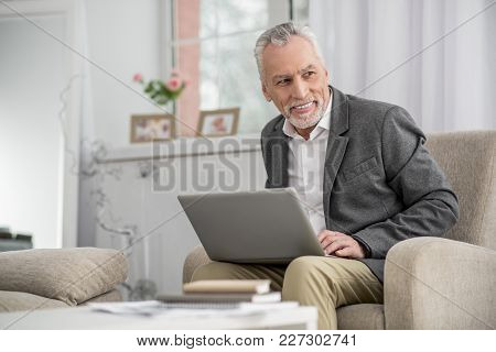 Have Idea. Handsome Bearded Man Keeping Smile On His Face And Looking Aside While Holding Laptop On