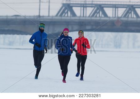 Group Of Young Athletes Running Technically In Winter Forest, Sport And Leisure Concept