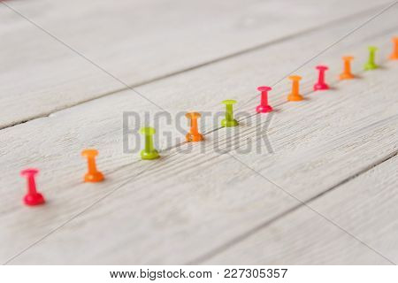 Colorful Pushpins Arrayed In Row Upscale On White Wooden Background, Copy Space. Stationery. Rise Bu