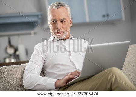 So Pleased. Cheerful Businessman Keeping Smile On His Face And Holding Laptop On Knees While Looking