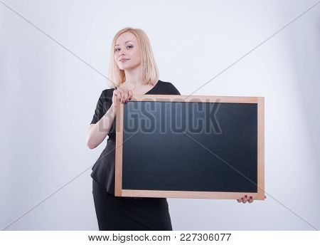 Close Up Of Business Woman With Chalk Board In Black Dress Isolated On White Background. Young Blond