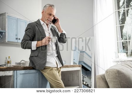 Important Call. Cheerful Man Keeping Smile On His Face And Holding Telephone Near Left Ear While Loo