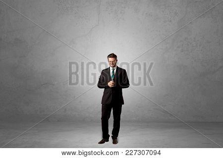 Alone handsome businessman standing in a dark empty room