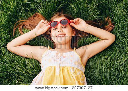 Outdoor Portrait Of Pretty Little Girl Wearing Heart Shaped Sunglasses, Lying On Fresh Green Grass.
