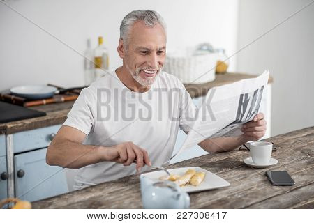 Morning Routine. Happy Bearded Man Keeping Smile On His Face While Reading Article And Having Breakf